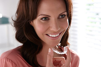 Photo of woman holding retainers